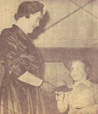 Florence Harbinson presenting the scissors to Mrs. W. Moore before she unfurled the new banner